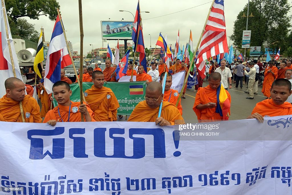 Cambodian Buddhist Monks Hold A Banner And International Flags As