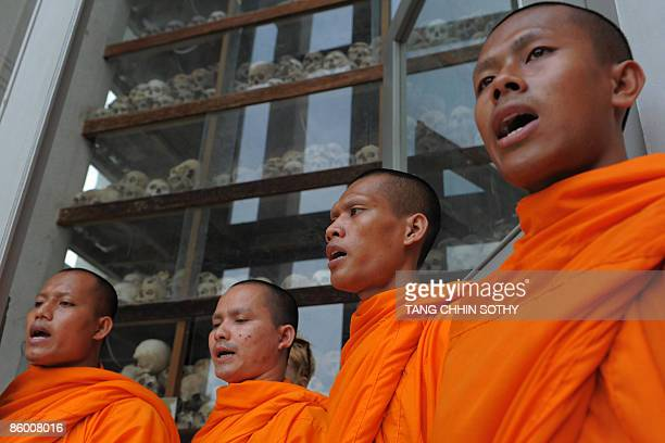 Cambodian Buddhist monks pray in front of skulls displayed at the Choeung Ek center built on the 'killing fields' in Phnom Penh on April 17, 2009....