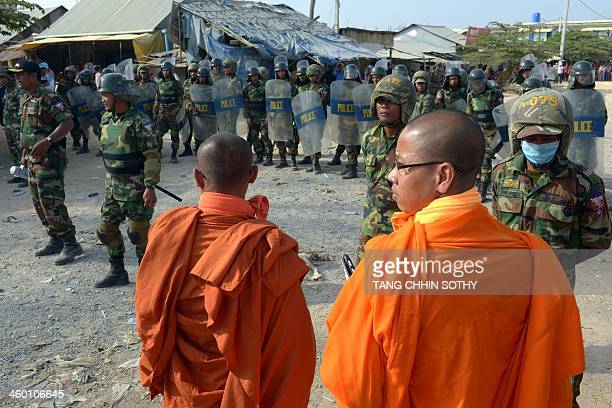 Cambodian Buddhist monks stand as soldiers stand guard during a garment workers' protest to demand higher wages in front of a factory in Phnom Penh...