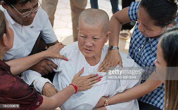 A Cambodian buddhist nun is assisted by people after she was overcome by emotion after praying over the death of former king Norodom Sihanouk in...