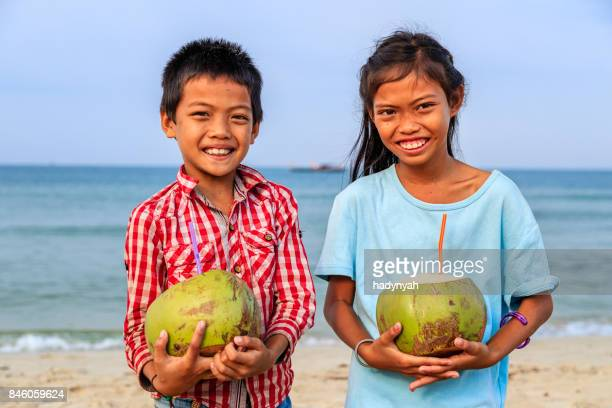 Cambodian children holding coconuts on the beach, Cambodia