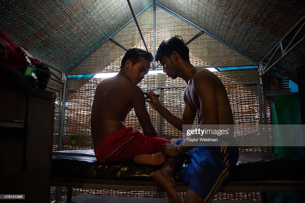 Cambodian circus artists prepare before a show by drawing on tattoos using marker on July 1, 2015 at Phare - The Cambodian Circus in Siem Reap, Cambodia. Phare Ponleu Salpak is an organization providing free education and artistic training to Cambodian children. Students in the organization's circus program often go on to careers performing both internationally and domestically at venues like Phare - The Cambodian Circus in Siem Reap.