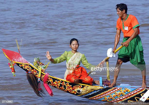 Cambodian couple in traditional dress perform on a boat during to celebrate the Water Festival along the Mekong River in Phnom Penh 08 November 2003...