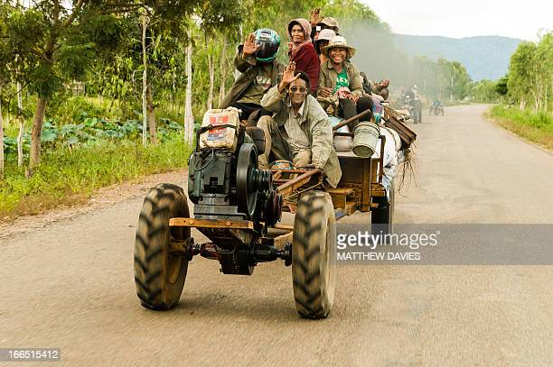 CONTENT] Cambodian Farmers Smile And Wave As They Ride On A Tractor Like Vehicle On A Road Near Siem Reap In Cambodia