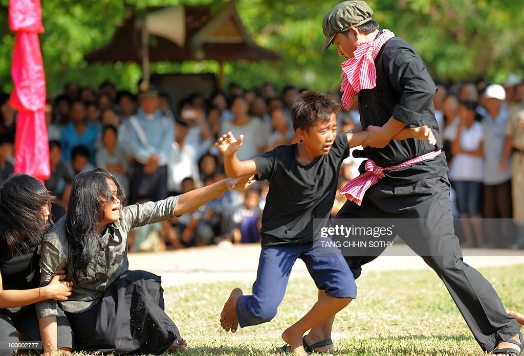 Cambodian fine arts school students take part in a performance to mark the annual 'Day of Anger' at the Choeung Ek killing fields memorial near Phnom Penh on May 20, 2010. Tearful Cambodians marked an annual 'Day of Anger' with a re-enactment of Khmer Rouge crimes at a notorious 'killing field' on May 20, to commemorate their relatives killed by the ruthless regime.