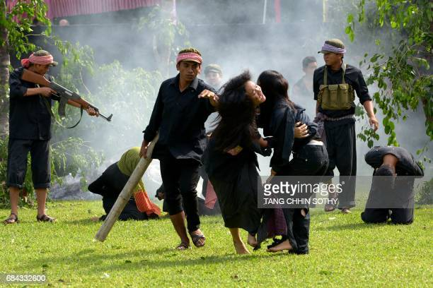 Cambodian fine arts school students take part in a performance to mark the annual 'Day of Anger' at the Choeung Ek killing fields memorial in Phnom...