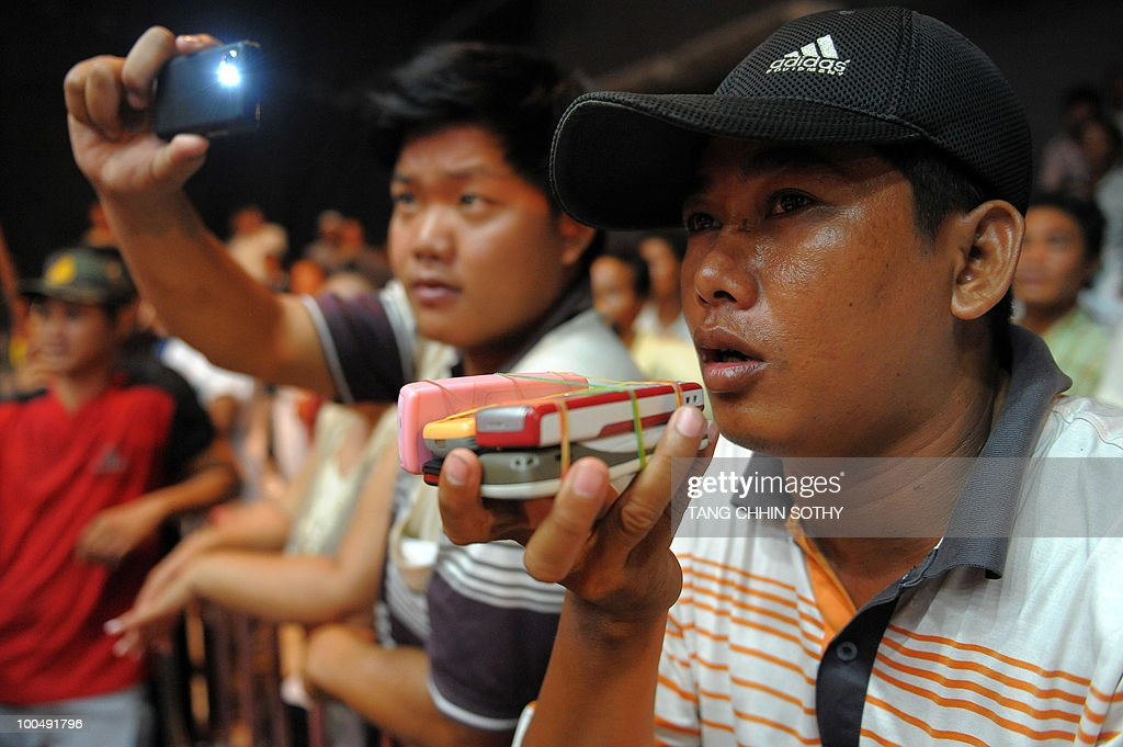 A Cambodian gambler talks on several mobile phones as he bets during a boxing match organised at a television station in Phnom Penh on May 15, 2010.