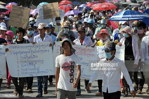 Cambodian garment factory workers march along a street during a protest in Phnom Penh on September 5, 2013. Thousands of Cambodian garment factory...