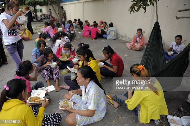 Cambodian garment wokers eat food in front of a garment factory in Phnom Penh on November 24, 2011. Cambodia has boosted healthcare for garment and...