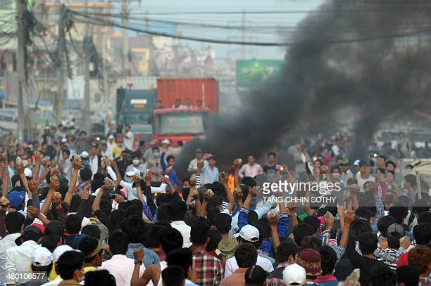 Cambodian garment workers carry rocks as they shout slogans after a brief clash with police during a protest to demand higher wages in front of a...