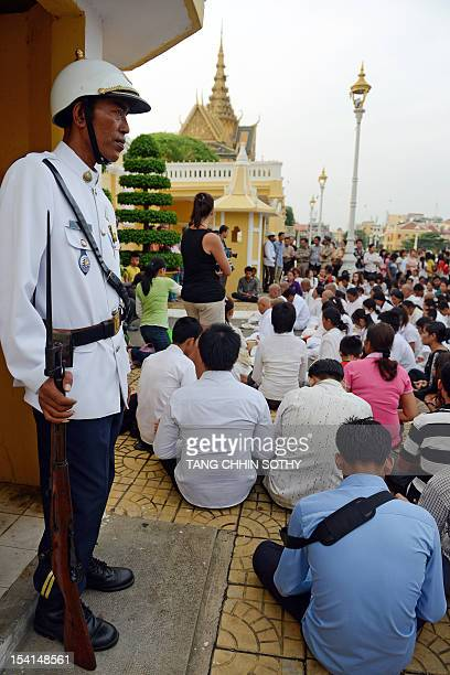 A Cambodian guard stands watch as laymen nuns and people pray in front of the Royal Palace in Phnom Penh on October 15 2012 to mourn the death of the...