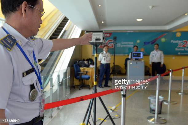 A Cambodian health official gestures towards a thermal scanner used to monitor the body temperatures of arriving passengers at Phnom Penh...