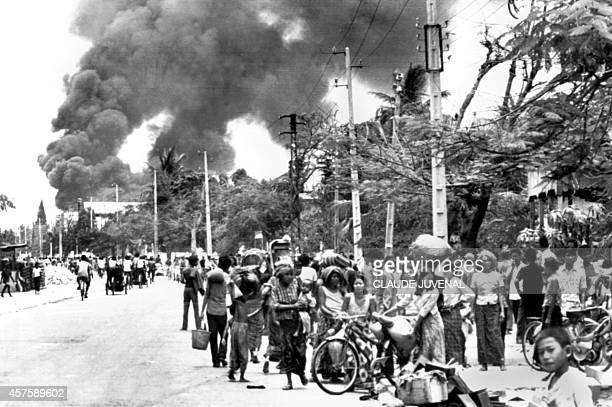 Cambodian inhabitants wait in a street of Phnom Penh 17 April 1975 as the gasoline depot burns before the Khmer Rouge enter the capital and establish...