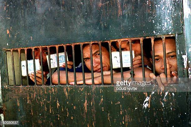 Cambodian inmates of Phnom Penh's T3 prison where hundreds of political prisoners have been held over the years show their voter cards before voting...