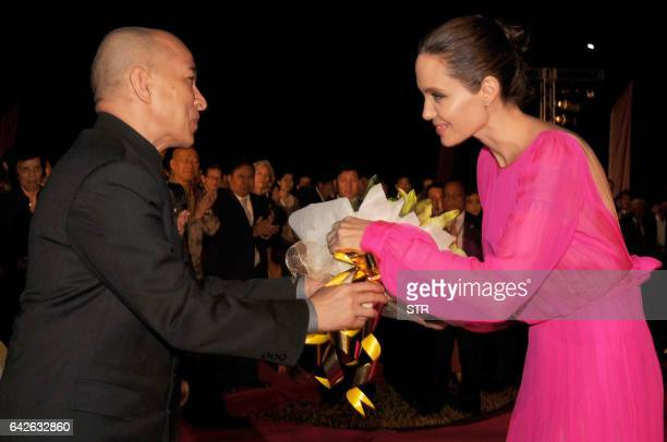 Cambodian King Norodom Sihamoni gives flowers to Hollywood star Angelina Jolie during the premiere of Jolie's new film 'First They Killed My Father'...
