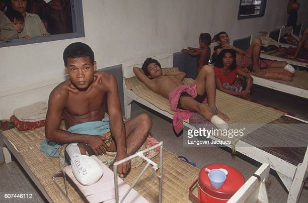 Cambodian land mine victims with amputated legs wait on cots in a primitive hospital ward French soldiers of the Foreign Legion intervening through a...
