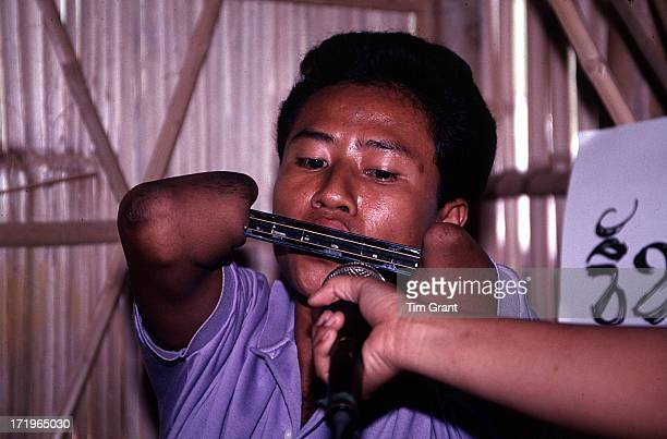 Cambodian landmine victim entertains us with his clever harmonica playing. Khoa I Dang Refugee Transit Camp. Thai / Cambodian Border.