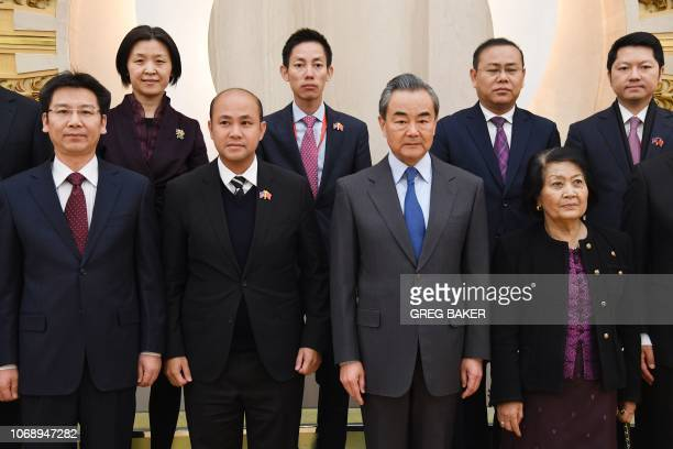 Cambodian lawmaker and President of the Union of Youth Federations of Cambodia Hun Many poses for a photo with China's Foreign Minister Wang Yi...