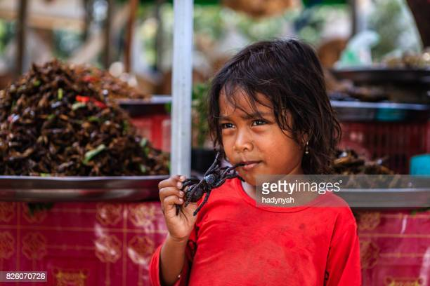 Cambodjaanse weinig meisje eten diepe gebakken tarantula, straatmarkt, Cambodja