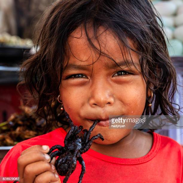 Cambodian little girl eating deep fried tarantula, street market, Cambodia