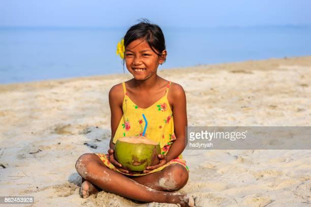 Kambodschanische Mädchen halten Kokosnuss am Strand, Kambodscha