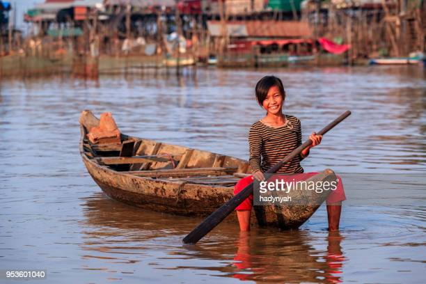 cambodian little girl rowing a boat, tonle sap, cambodia - traditionally cambodian stock pictures, royalty-free photos & images