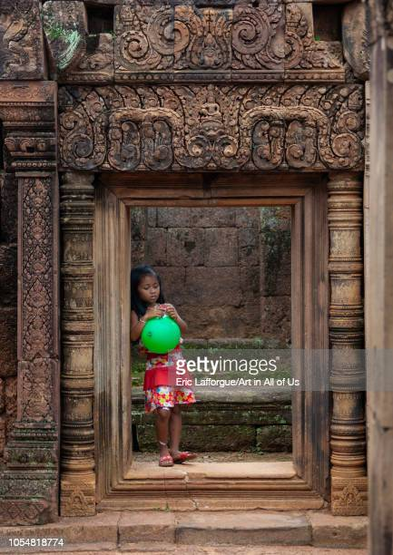 Cambodian little girl with a green balloon in Banteay Srei temple gate Siem Reap Province Angkor Cambodia on July 26 2006 in Angkor Cambodia