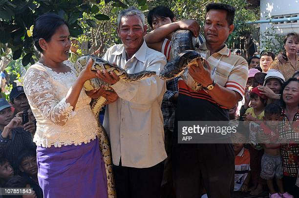 A Cambodian man carries his female pet python called Chamreun as a woman carries her male pet python called Krong Pich during a wedding ceremony in...