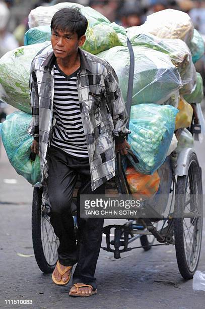 A Cambodian man pulls his cyclo loaded with vegetables at a market in Phnom Penh on March 16 2011 While still among one of the world's poorest...
