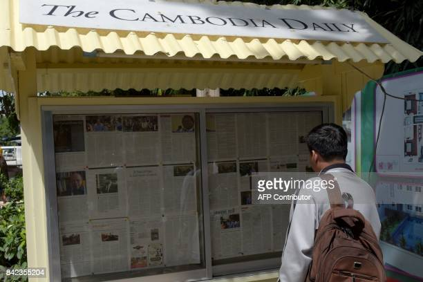 A Cambodian man reads the Englishlaguage newspaper Cambodia Daily at the information board in front of its office in Phnom Penh on September 4 2017...