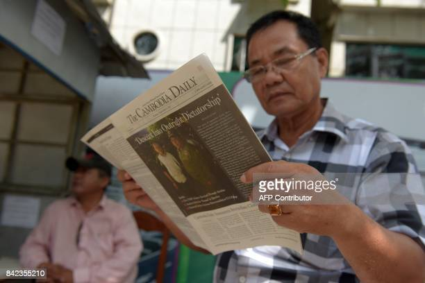 A Cambodian man reads the Englishlaguage newspaper Cambodia Daily in Phnom Penh on September 4 2017 One of Cambodia's few remaining independent...