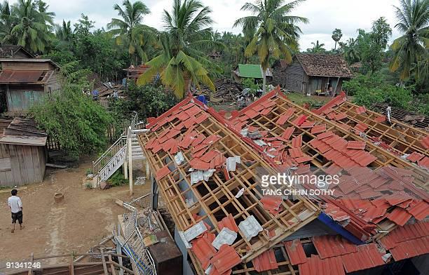 A Cambodian man walks past a house damaged by Typhoon Ketsana in Kampong Thom province 168 kilometres north of Phnom Penh on October 1 2009...