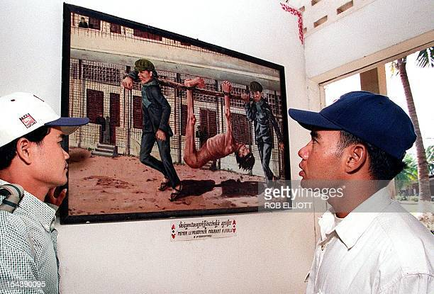 A Cambodian man walks past a painting depicting torture inflicted during the Pol Pot regime at one of the Cambodian capital's most frequented...