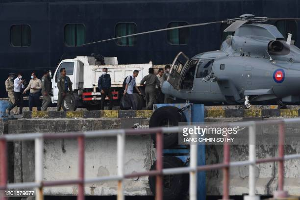 A Cambodian medic carries samples from people onboard the Westerdam cruise ship to a helicopter in Sihanoukville on February 18 as authorities...