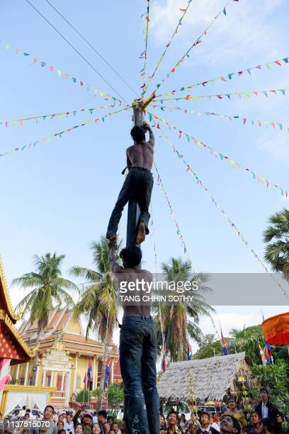 Cambodian men play a popular game as they climb an oiled pole during Khmer New Year celebrations at a pagoda in Kandal province on April 16 2019