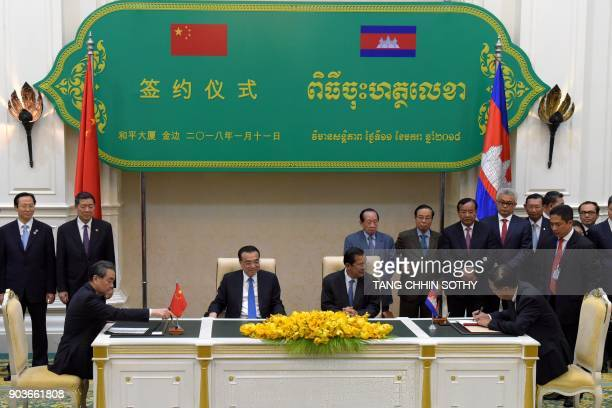 Cambodian Minister of Commerce Pan Sorasak signs with Chinese Minister of Foreign Affairs Wang Yi as Cambodian Prime Minister Hun Sen and Chinese...