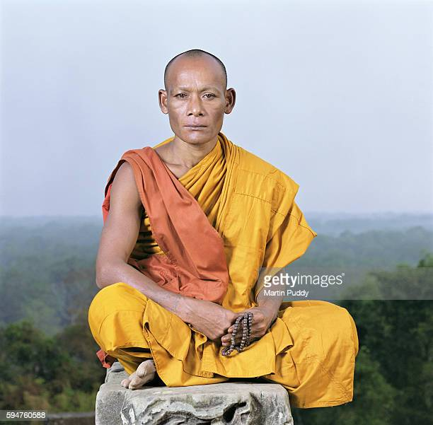 Cambodian monk sitting on pillar at temple