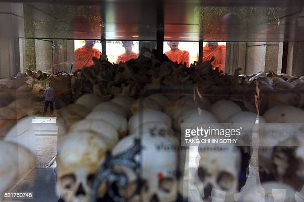Cambodian monks pray in front of skulls of those killed by the Khmer Rouge regime at the Choeung Ek killing fields memorial in Phnom Penh on April 17...