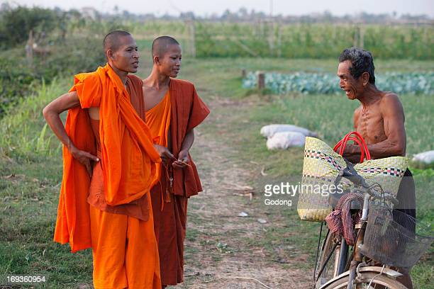 Cambodian monks speaking with a farmer Cambodia