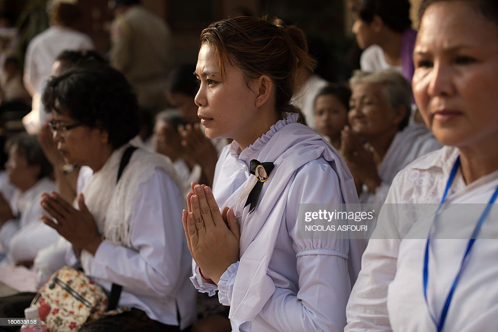 Cambodian mourners sit and pray in a street in front of the crematorium where a coffin bearing the remains of Cambodia's late King Norodom Sihanouk is placed before his cremation, near the Royal Palace in Phnom Penh on February 4, 2013. Thousands of mourners massed in the Cambodian capital as the kingdom cremated its revered former King Norodom Sihanouk, who steered his country through six turbulent decades. AFP PHOTO/ Nicolas ASFOURI