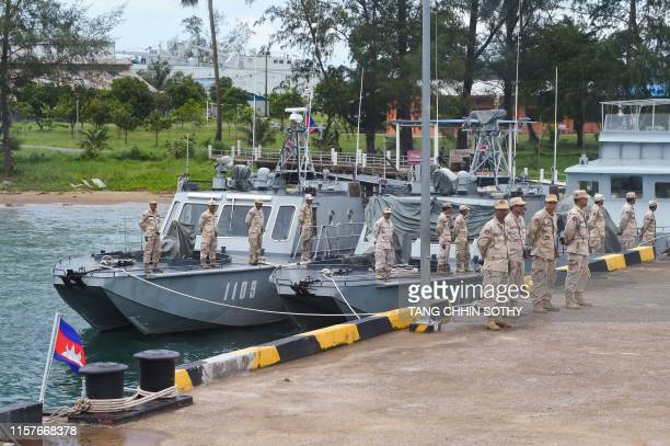 Cambodian navy personnel stand in formation on boats berthed at a jetty in Ream naval base in Preah Sihanouk province during a government organized...