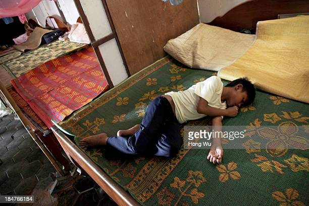 Cambodian orphan sleeps on the bed in a nongovernment orphanage on September 28 2013 in Siem Reap Cambodia The devastation caused by the Khmer Rouge...