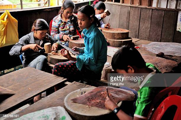 Cambodian orphans carve the cowhide handicrafts selling to tourists to earn living costs in a nongovernment orphanage on September 28 2013 in Siem...