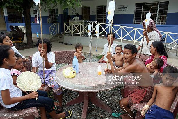 Cambodian parents hold serums to treat dengue fever for their children as they sit outside Takeo Hospital province some 78 kilometers south of Phnom...