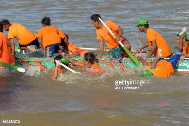 Cambodian participants jump off their dragon boat before it sank during the Water Festival on the Tonle Sap river in Phnom Penh on November 2 2017...