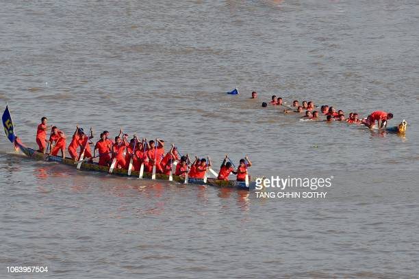Cambodian participants row their dragon boat passing by a capsizing team during a rehearsal for the annual Water Festival on the Tonle Sap river in...