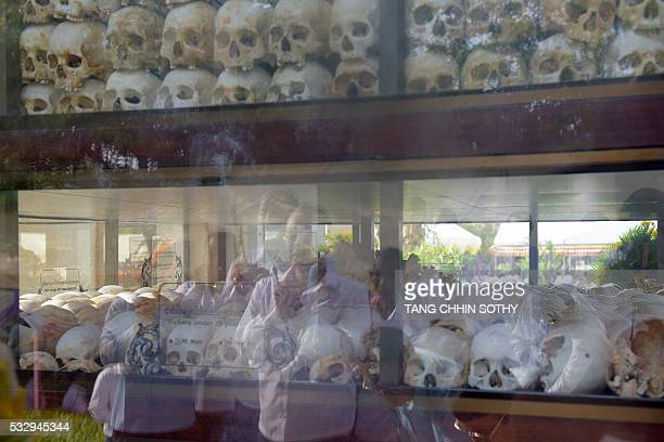 Cambodian people are reflected in the door of a building containing skulls as they pray to mark the annual 'Day of Anger' at the Choeung Ek killing...