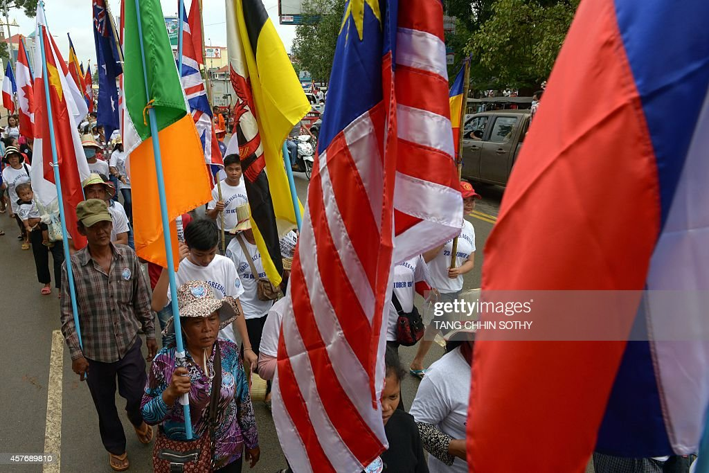 Cambodian People Hold International Flags As They March To Mark The