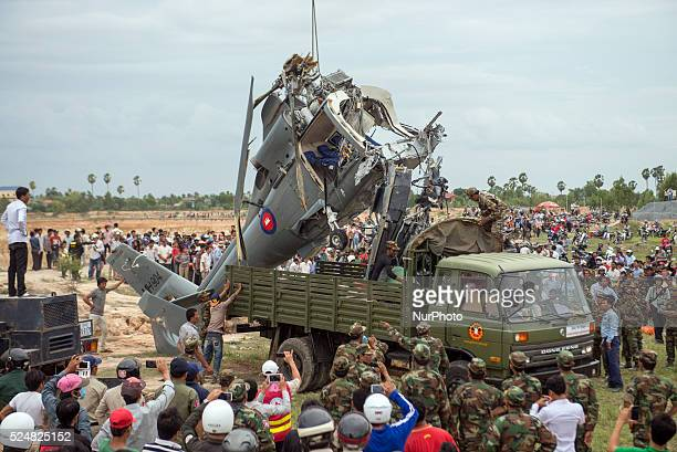 Cambodian people look at a damaged helicopter after it crashed on the outskirts of Phnom Penh on 14 July 2014 According to offical Four Cambodian...