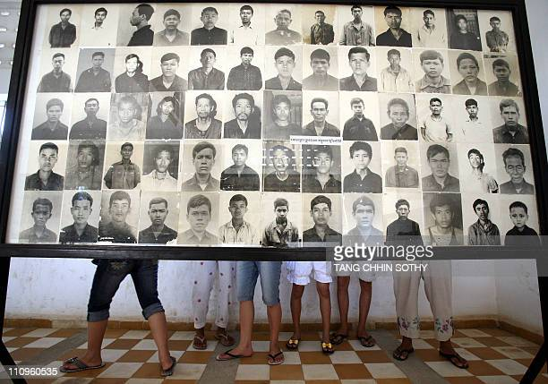Cambodian people look at Khmer Rouge victims portraits on a board at Tuol Sleng genocide museum in Phnom Penh 13 June 2007 A panel of Cambodian and...